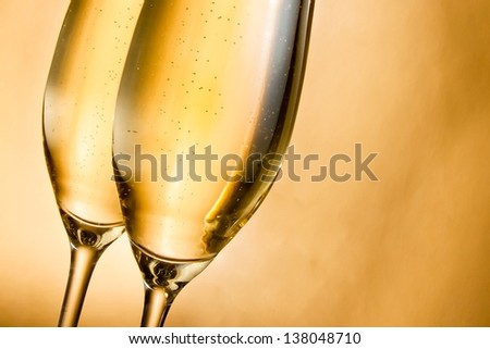 flutes of champagne with golden bubbles against golden background - stock photo