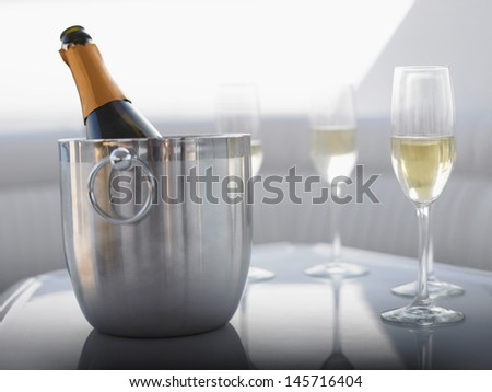 Flutes with champagne bottle in ice bucket on table - stock photo