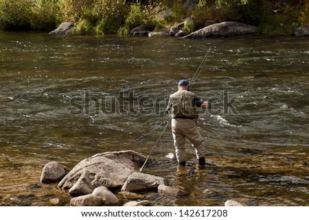 Fly fisherman at Taylor River, Colorado. - stock photo
