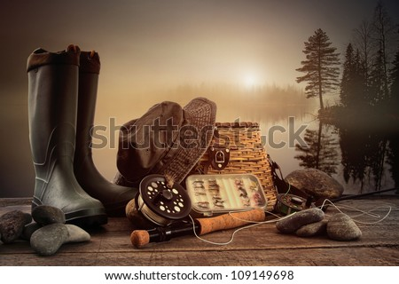Fly fishing equipment on deck with view of a misty lake background - stock photo