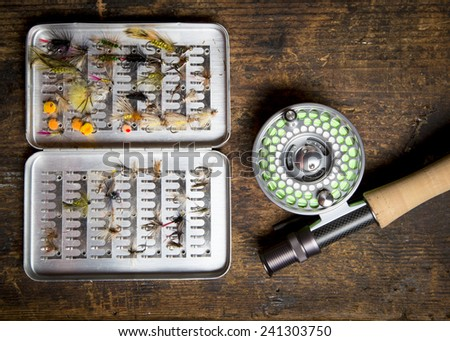 Fly fishing gear, which includes a reel, pole, and containers of flies.   - stock photo