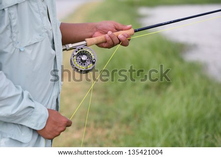 Fly fishing in hand - stock photo