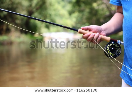 fly fishing rod in hand. - stock photo
