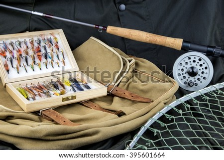 Fly fishing tackle with bag and net on outdoor coat - stock photo