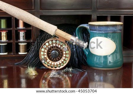 Fly Rod being prepared for a day of fly fishing.  Coffee mug with blank area for printing message - stock photo