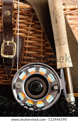Fly rod is in front of old creel - stock photo