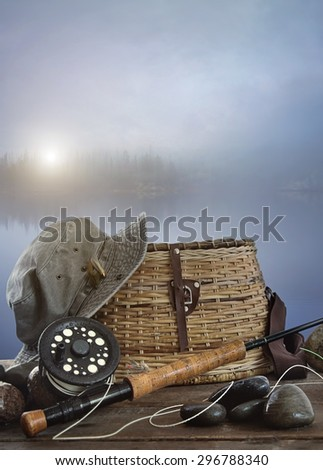 Fly rod with creel and equipment on wood table - stock photo