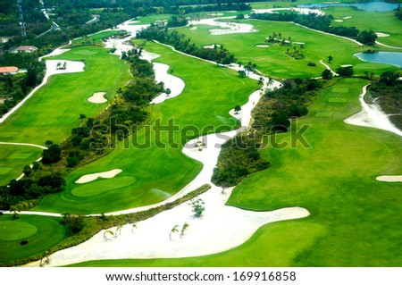 Flying above a golf course at an exotic destination - stock photo