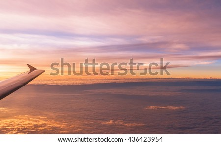 Flying aircraft wind on sunset sky view from window of airplane - stock photo