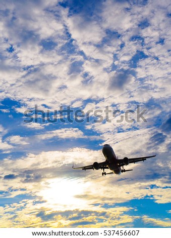 flying airplane in the morning or evening with low gold sun light in the blue cloudy sky