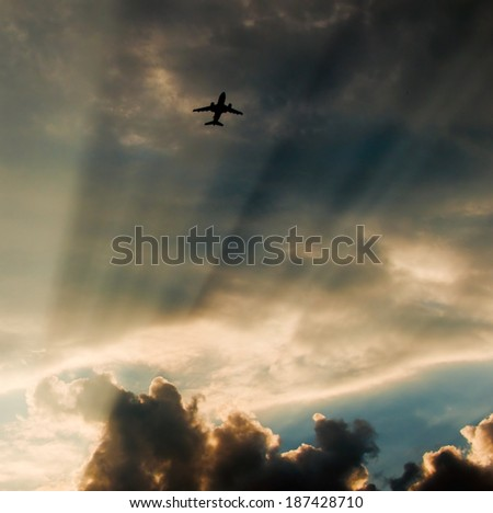 Flying airplane on dramatic sky. sun rays through clouds - stock photo