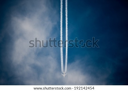Flying airplane on the blue sky leaving white lines contrail behind - stock photo