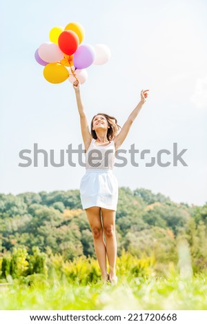 Flying away. Happy young woman holding colorful balloons and flying over a green meadow - stock photo