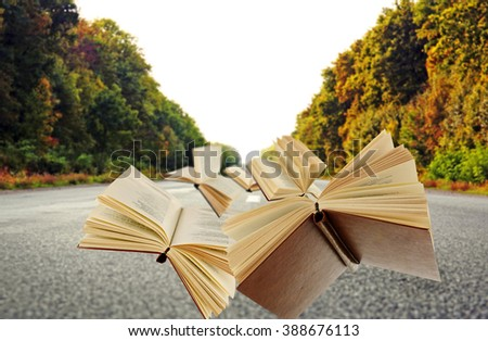 Flying books on asphalt road and trees background