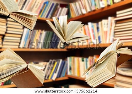 Flying books on library bookshelves background - stock photo