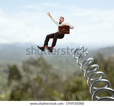 flying businessman and huge metal spring - stock photo
