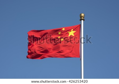 Flying Chinese National Flag against blue sky