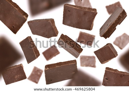 Flying chocolate pieces on white background