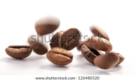 Flying coffee beans on a white background, close-up - stock photo