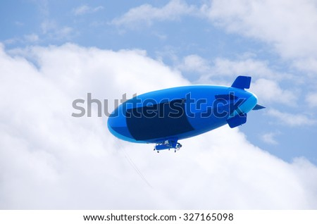 Flying colorful blimp with a blank advertising sign area to accommodate your message. Fluffy clouds and blue sky in the background. - stock photo
