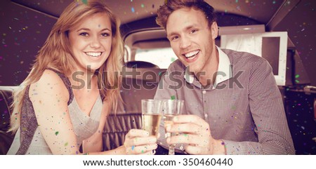 Flying colours against happy couple drinking champagne in limousine - stock photo
