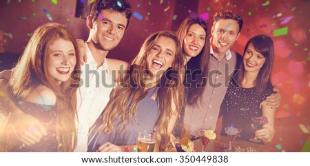 Flying colours against happy friends on a night out together - stock photo
