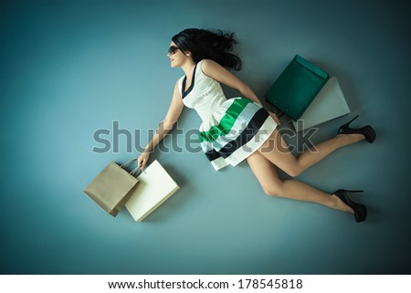Flying girl with packages in studio - stock photo