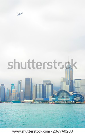 Flying helicopter in Hong Kong sky in the misty morning - stock photo