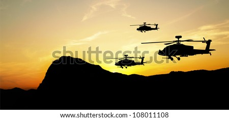 Flying helicopter silhouettes on sunset background