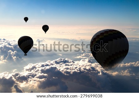 Flying hot air balloon over the clouds in cloudy sky. - stock photo