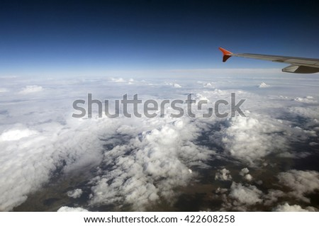Flying in an airplane between the white clouds.  Fluffy white clouds view from above in sky. The wing of the plane cuts the atmosphere in the air. - stock photo