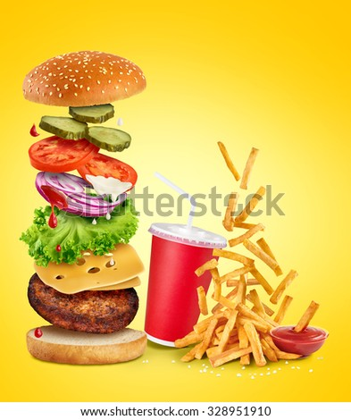 Flying ingredients of hamburger, fried potatoes, ketchup and paper cup.  - stock photo