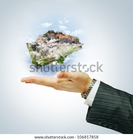Flying island on businessman's hand - stock photo