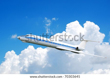 Flying jet airplane against blue cloudy sky