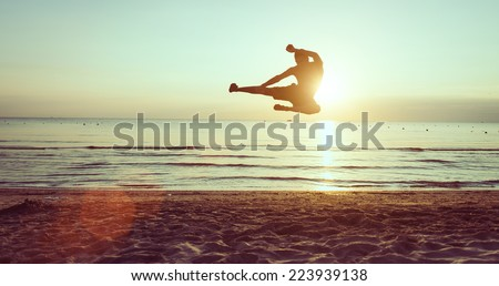 flying kick on the beach at dawn. martial arts and fitness - stock photo