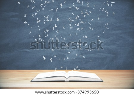 Flying letters from the opened book on wooden table at blackboard background - stock photo
