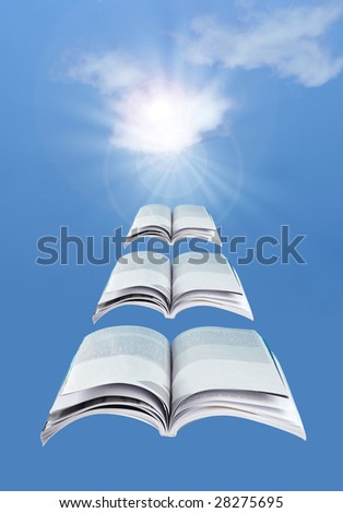 Flying open books over a blue sky - stock photo