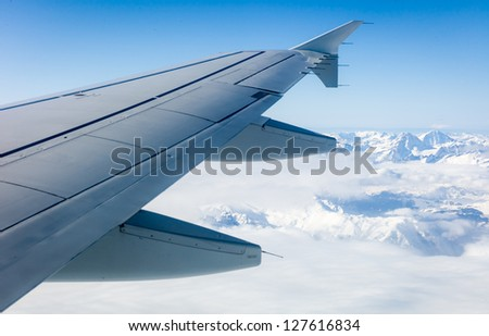 Flying over the Alps - view of airplane wing over snow capped mountains - stock photo