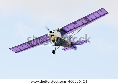 Flying private propeller-driven airplane over blue sky - stock photo
