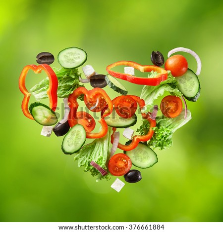 flying salad isolated on green background. Greek salad: red tomatoes, pepper, cheese, lettuce, cucumber and olives - stock photo