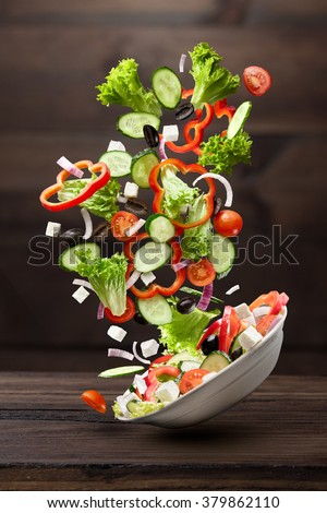 flying salad isolated on wooden background. Greek salad: red tomatoes, pepper, cheese, lettuce, cucumber and olives - stock photo