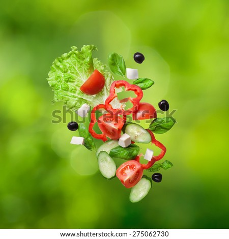 flying salad on natual green backround - red tomatoes, pepper, cheese, basil, cucumber and olives - stock photo