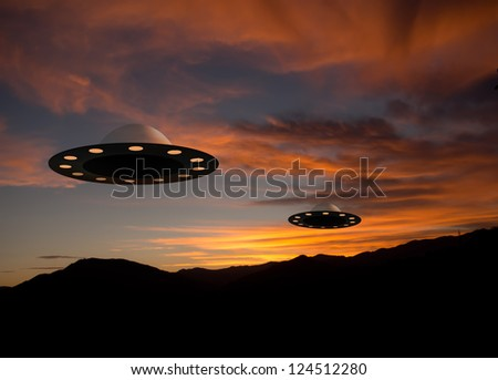 Flying saucer UFOs at sunset - alien space craft - stock photo