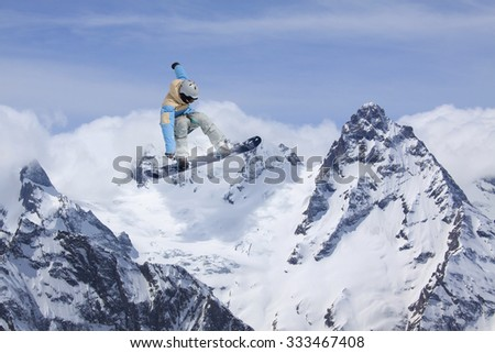 Flying snowboarder on mountains, extreme winter sport - stock photo