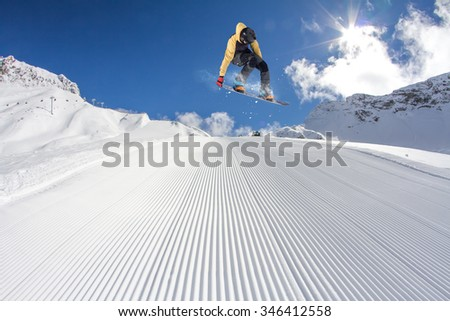 Flying snowboarder on mountains. Extreme winter sport. - stock photo