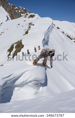 Flying snowboarder on mountains. Extreme winter sport.