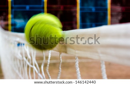 Flying tennis ball hits the white tennis net - stock photo