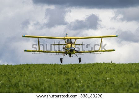 Flying the Fields/An aerial applicator sprays a field of green peas for insects. - stock photo