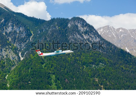 flying turboprop airplane against apls mountains background - stock photo