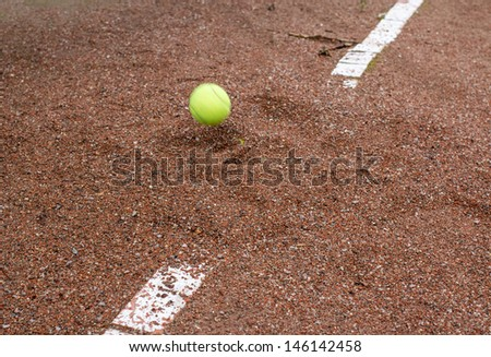 Flying yellow ball and Old tennis court surface is red and ruined the line marking - stock photo